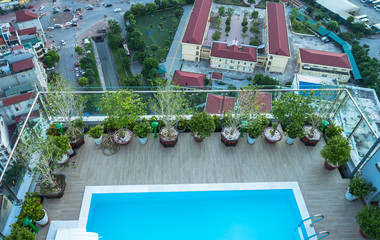 Balcony with closeup swimming pool, home grown flowers of high rise building in the city.