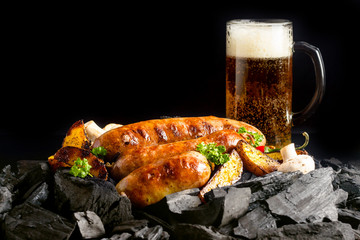 Sausages grilled over charcoal with a beer in the background