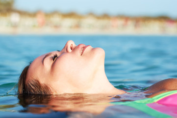 Young girl lying on sea water.