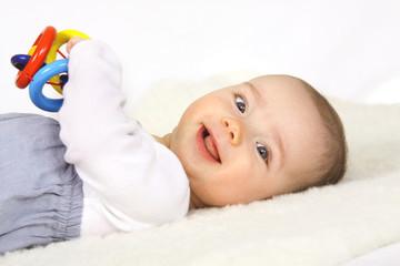 Ein Baby spielt mit einem Holzspielzeug