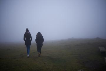 dos personas caminando hacia la niebla