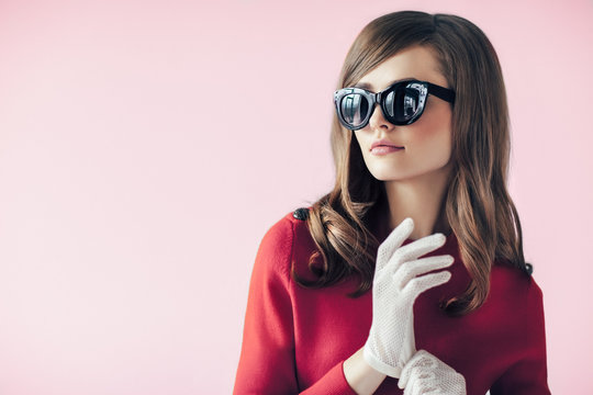 Fashion retro style portrait of young beautiful woman in sunglasses on pink background