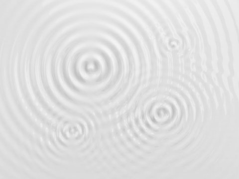 Ripples on a white liquid surface.