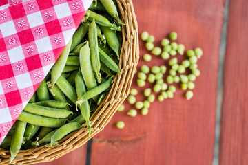 Unopened pea pods in a basket on wooden background.
