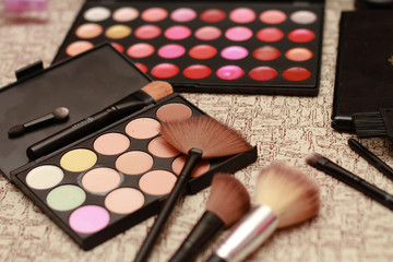 Cosmetic palette with the shadows lying on the table. Cosmetic makeup, women's beauty