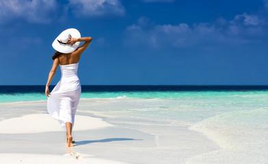 Attraktive Frau in weißem Kleid läuft auf einer Sandbank in den Tropen