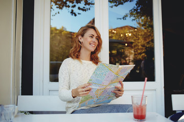 Happy Caucasian female searching on map the best route for visit city in her vacation time, young blonde hair woman sitting in coffee shop and with smile mentions the places which she visited
