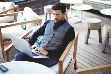 Young successful businessman working on a laptop while sitting in cafe during work break lunch,thoughtful entrepreneur connecting to wireless via computer, intelligent male freelancer work on net-book