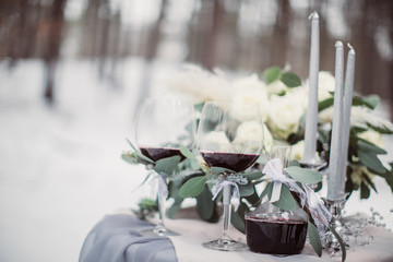 Beautiful stylish wedding glasses and bouquet on the table outside
