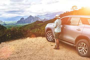 Garden Poster Brown Young hipster man is looking away, while is standing near his rental automobile on a hill in Thailand. Male tourist is enjoying fantastic jungle view during long awaited summer trip on suv in Asia