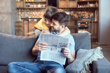 Happy little boy hugging father reading newspaper at home