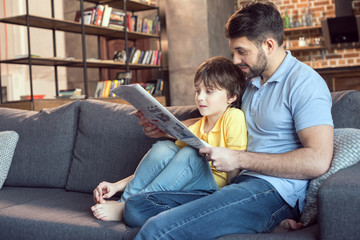 father and son reading newspaper together at home
