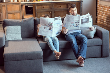 father and son sitting on couch and reading newspapers