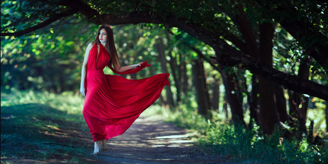 Photo of fashion sexy woman in red dress in fairy forest. Beauty springtime