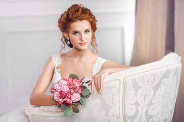 Bride in beautiful dress sitting resting on sofa indoors