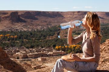 femme assise sur une montagne buvant de l'eau devant un village marocain