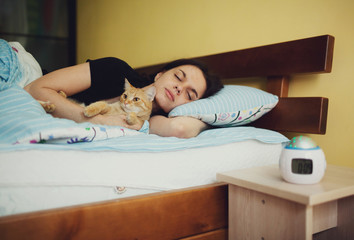 young  girl lying in bed with her red  cat