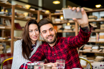 Couple at cafe bar, taking a photo.