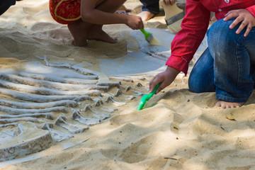 Children Excavating dinosaur fossils simulation  in the park