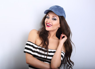 Beautiful tooth smiling young make-up model in fashion blue cap posing on blue background with empty copy space. Long brown hair style
