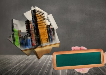 Composite image of Hand holding board against city architecture