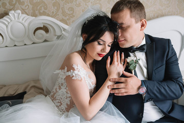 beautiful and young bride and groom sitting on the bed
