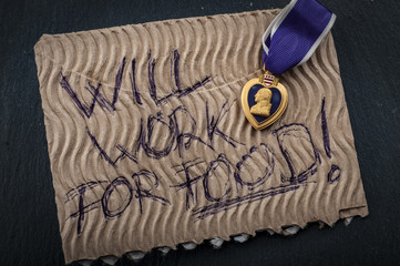 "Veterans reintegration and social issues concept with cardboard sign reading ""will work for food"" and a purple heart medal illustrating the reality of many veterans that struggle to join civilian life"