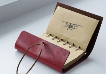 Leather notebook with black pen picture of an airplane