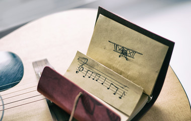 Leather notebook with black pen picture of an airplane and stave on the background of a guitar