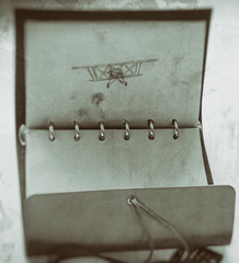 Old vintage photo of leather notebook with black pen picture of an airplane