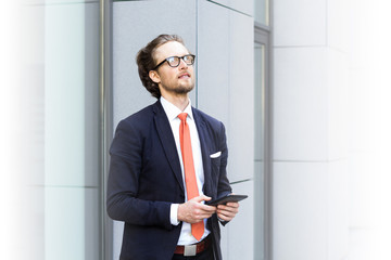 A businessman with a beard and wearing glasses looking up with hope of success. Space for text.