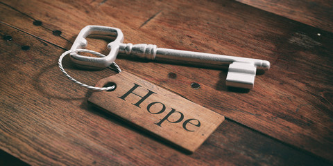Old key with tag hope on a wooden background. 3d illustration