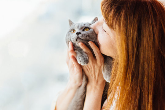 Close up of lovely middle-aged redhead woman kissing gray cat.