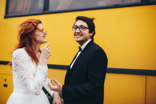 The brides standing near yellow bus