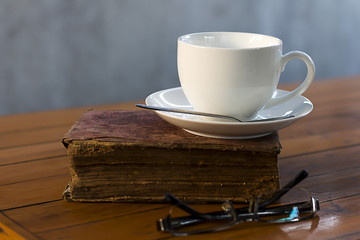 White coffee cups and old books on a wooden table.