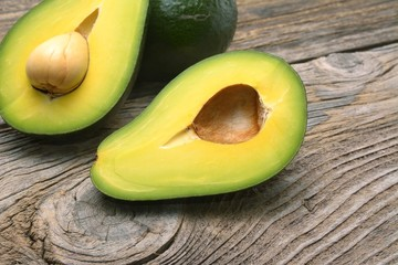 Wall Mural - avocados one cut in two with seed, on wooden surface