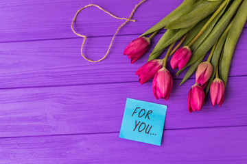 Pink colorful tulips over a purple background, in a flat lay composition with heart and inscription on paper for you.