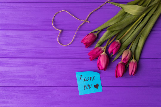 Pink colorful tulips over a purple background, in a flat lay composition with heart and inscription on paper i love you.