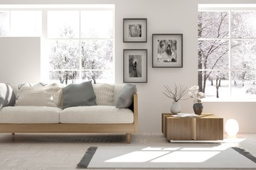 White room with sofa and winter landscape in window. Scandinavian interior design