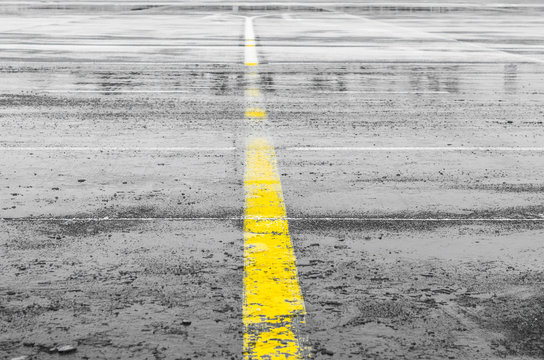 Wet steering track road. With yellow stripe separating the pointing on the pavement