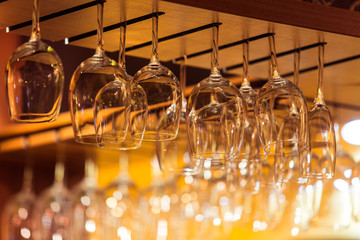 Empty glasses for wine above a bar rack in restaurant