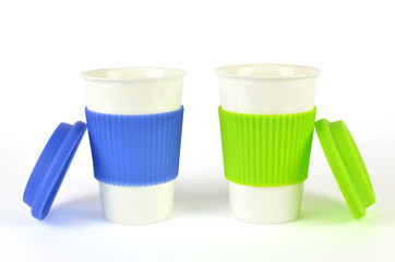 Two white containers for coffee or hot drinks with blue and green thermo sleeves and lids beside them, isolated on white
