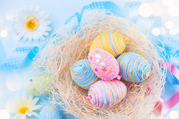 Fotoväggar - Easter. Beautiful colorful eggs with decorations over blue wooden background