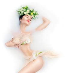 Beautiful fashion model girl taking milk bath, spa and skincare concept