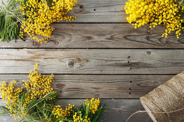 Mimosa flowers on gray wooden background. old wooden table. Copy space for text. twine roll
