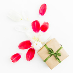 Tulip petals and gift box on white background. Flat lay, top view. Woman background.