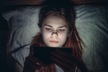 beautiful woman with a tablet in bed