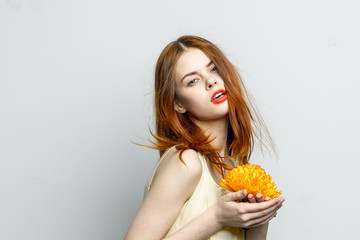 red-haired woman holding a yellow flower in hands