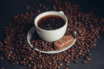 cup with a drink and coffee beans, candy...