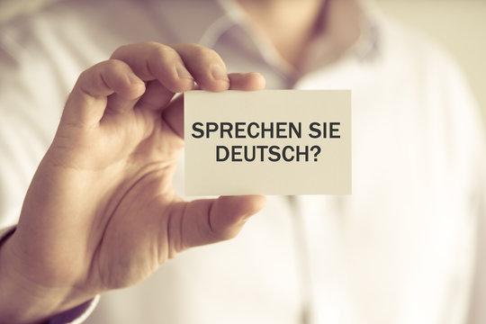 """Businessman holding message card """"Sprechen Sie Deutsch?"""" written in German - translation : Do you speak German?"""